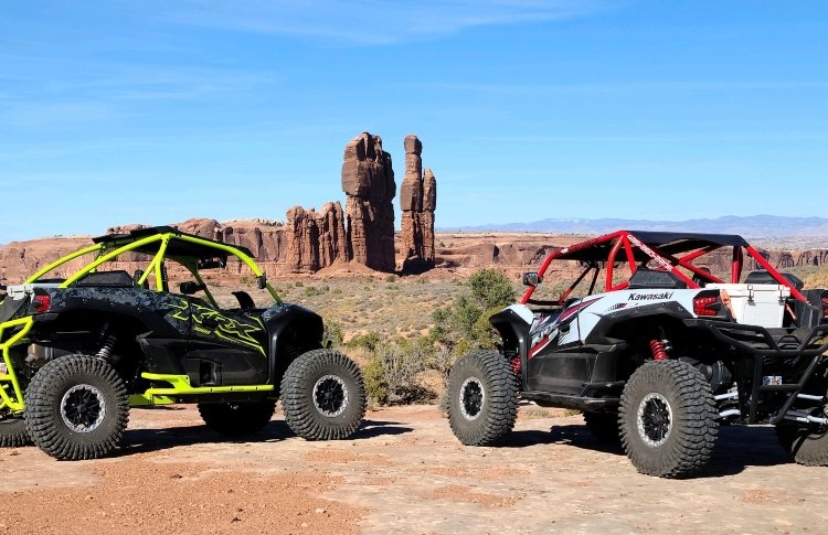 two utvs looking over a desert with vertical rock formations at the center