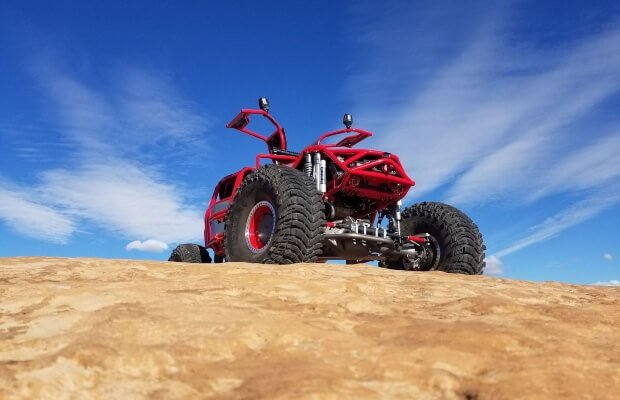 red custom 4x4 car looking over the edge